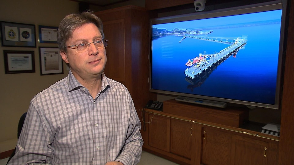 Le pdg du port de Sept-Îles, Pierre Gagnon devant une photo du quai multiusagers local