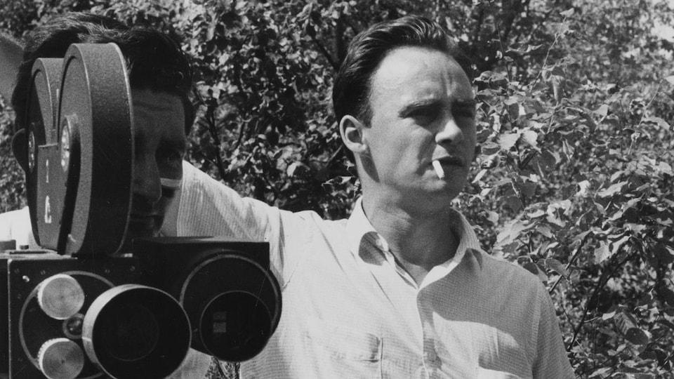 Pierre Gauvreau, cigarette à la bouche, lors d'un tournage extérieur à l'Île Perrot. Il se tient aux côté d'un caméraman.