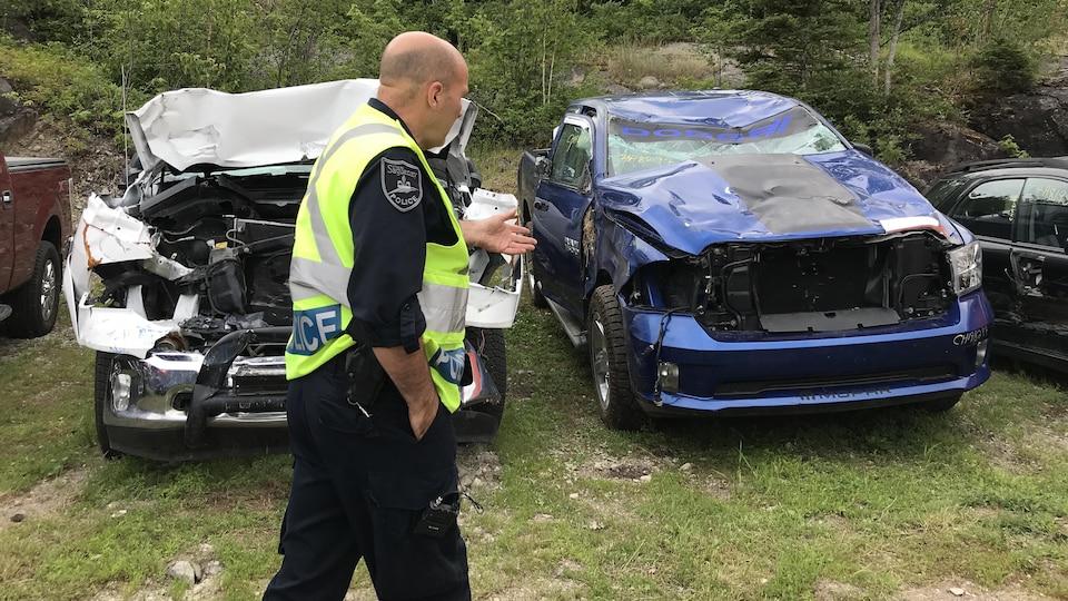 Pierre Girard devant deux camionnettes accidentées