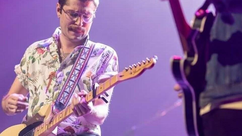 Pierre Guitard jouant de la guitare sur scène avec une chemise à motifs exotiques