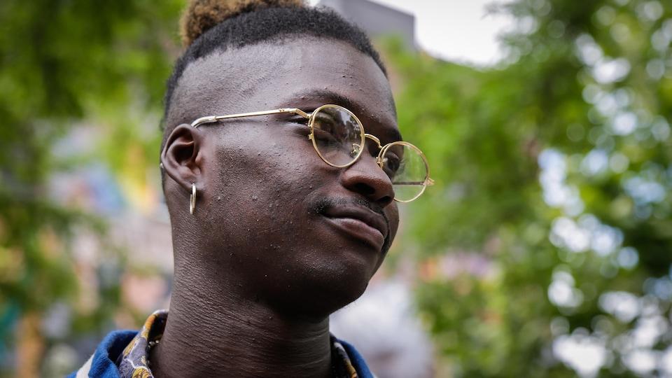 Un jeune homme noir regarde vers la droite en souriant, au milieu d'un parc.