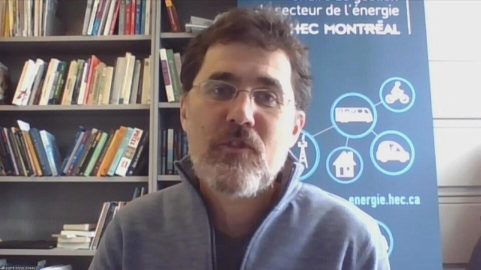 Pierre-Olivier Pineau devant une bibliothèque.
