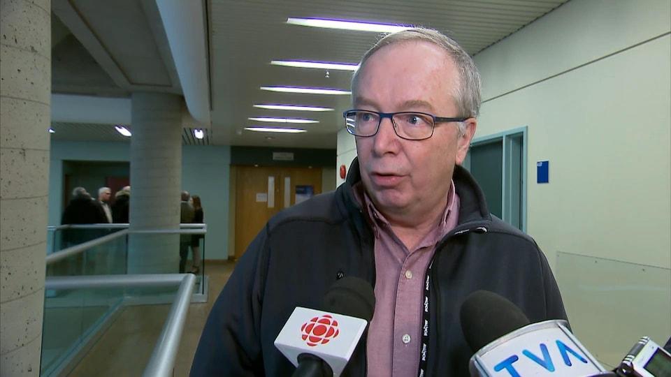 Pierre Pelchat répond aux questions des journalistes lors d'une mêlée de presse dans les couloirs du palais de justice de Québec.