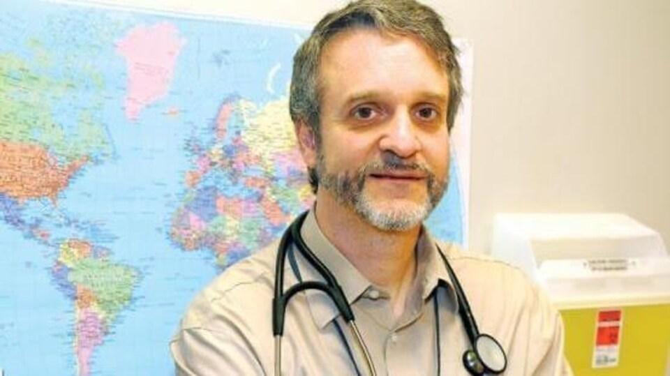 Dr Pierre Plourde porte un stéthoscope autour du cou. Il est photographié devant une carte du monde et d'un bac jaune contenant des déchets médicaux.