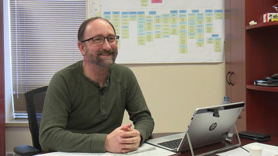 Pierre Rocque sourit, assis derrière son bureau.