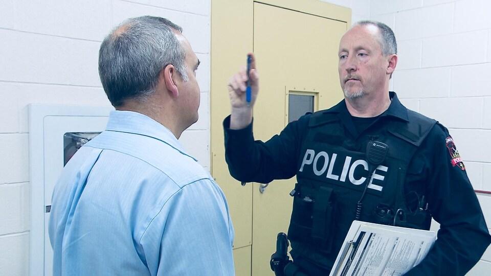 Un policier qui tient un objet dans sa main droite et un automobiliste debout devant lui.