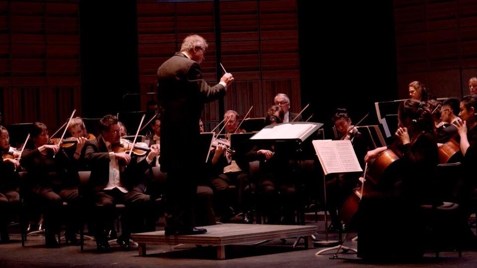Maestro Pierre Simard devant les musiciens du Vancouver Island Symphony.Tout juste derrière le chef d'orchestre, la section des cordes.