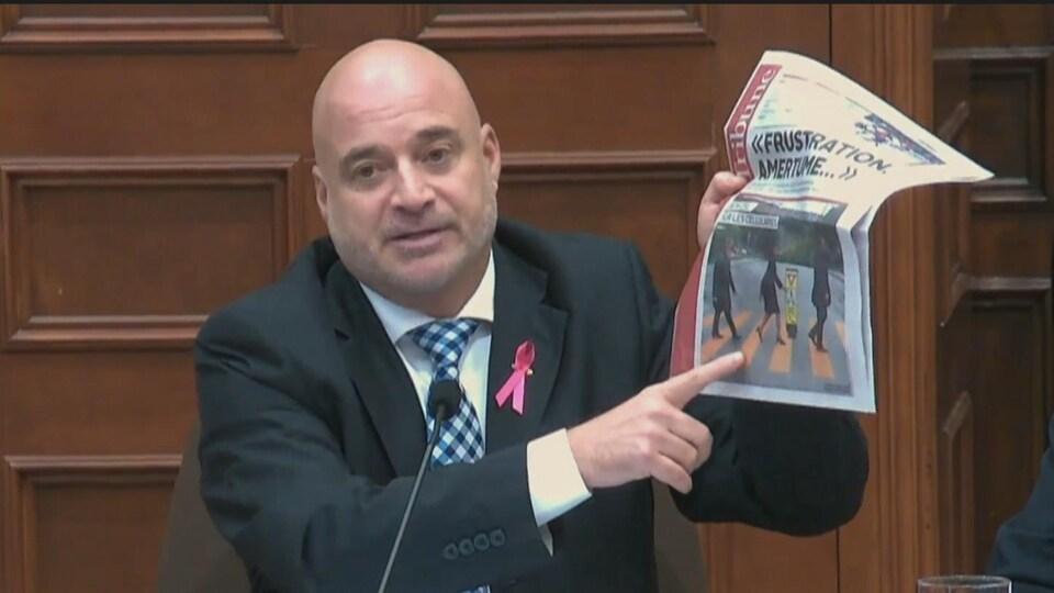 Pierre Tremblay tenant un journal entre ses mains pendant le conseil municipal de Sherbrooke.