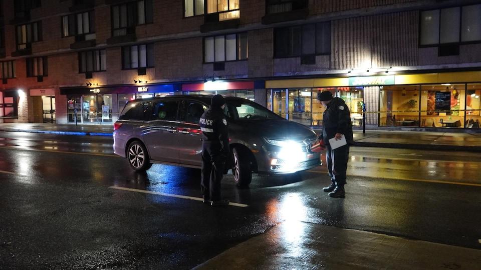 Des policiers inspectent le véhicule impliqué dans l'accident.