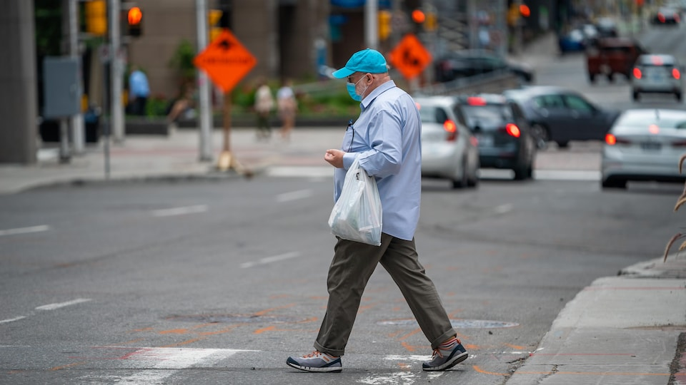 Un homme masqué traverse une rue d'Ottawa.