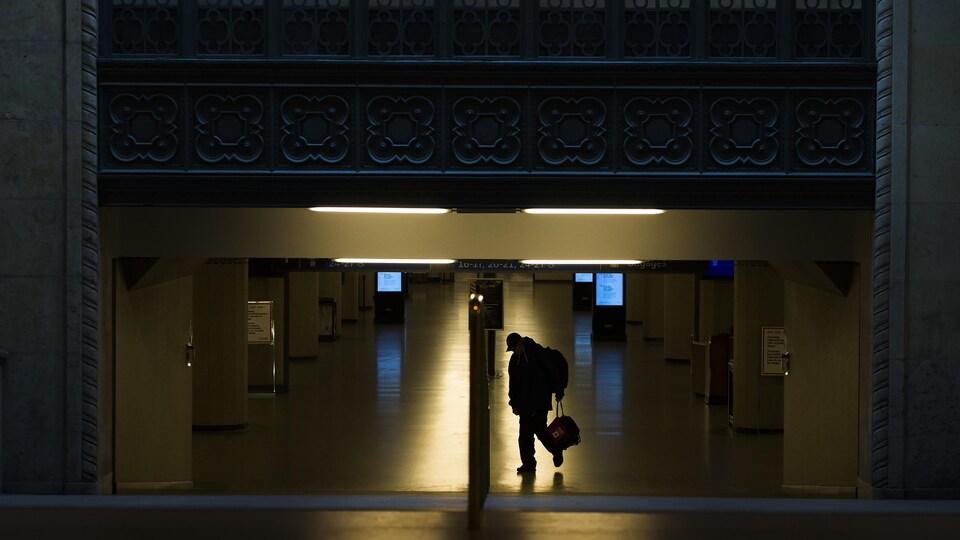 Un piéton marche seul devant la gare Union à Toronto.