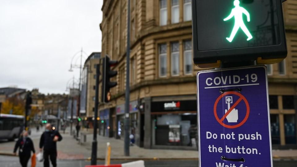 Des piétons à Bradford passent devant un panneau de feux de circulation, qui leur conseille de ne pas toucher le bouton à cause de la COVID-19.