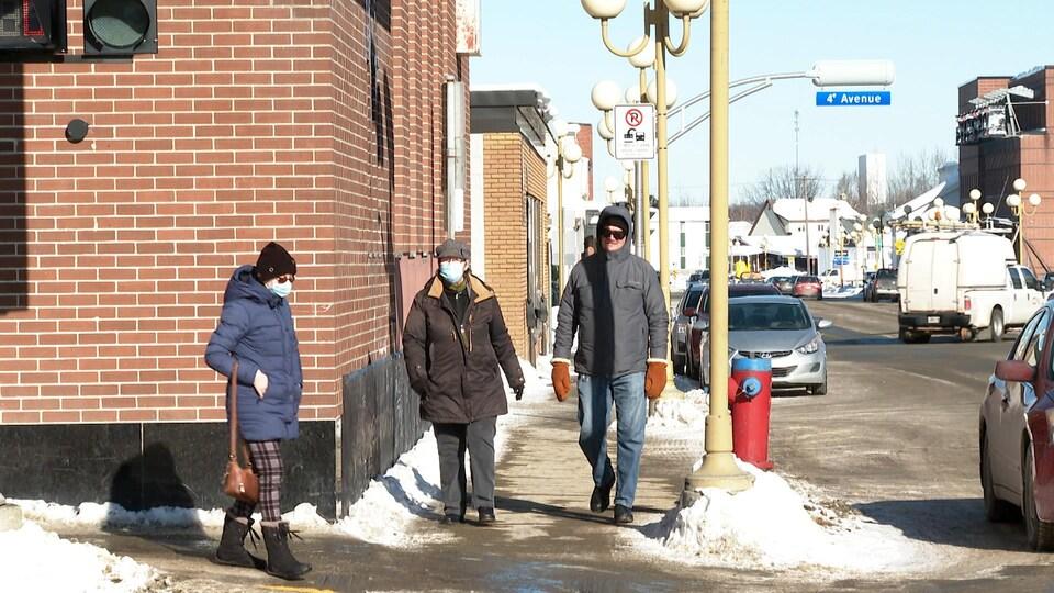 Des piétons circulent au centre-ville de Val-d'Or en hiver. Deux personnes portent un masque d'intervention.