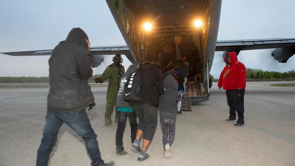 Des gens rentrent dans un avion Hercules.