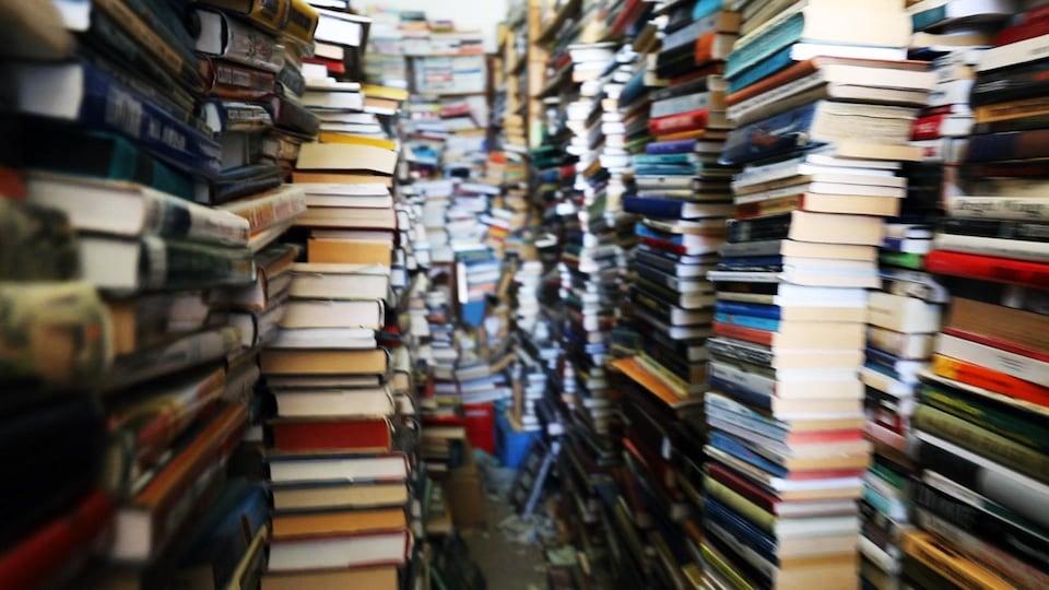 Des piles de livres s'accumulent dans une pièce étroite.