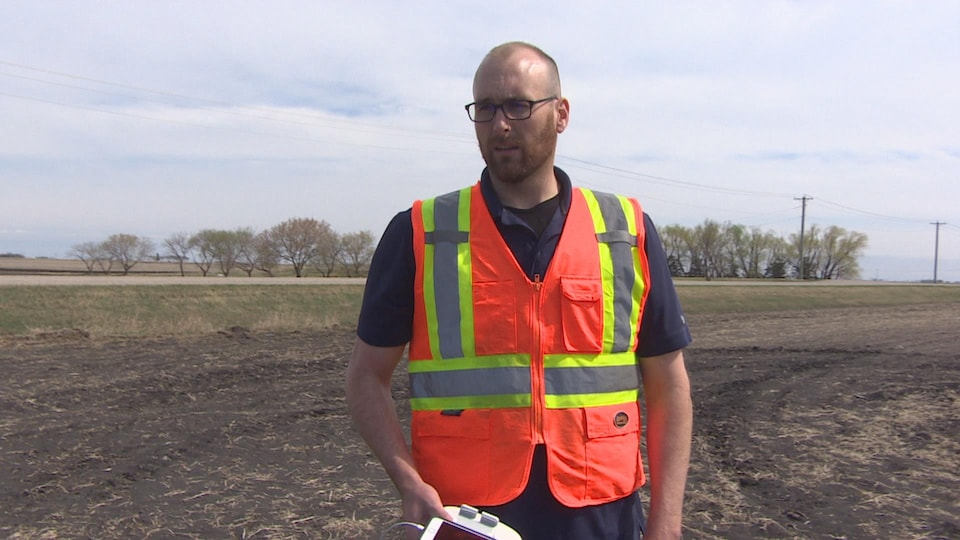 Un homme au milieu d'un champ, avec une veste de sécurité, qui tient une télécommande pour un drone.