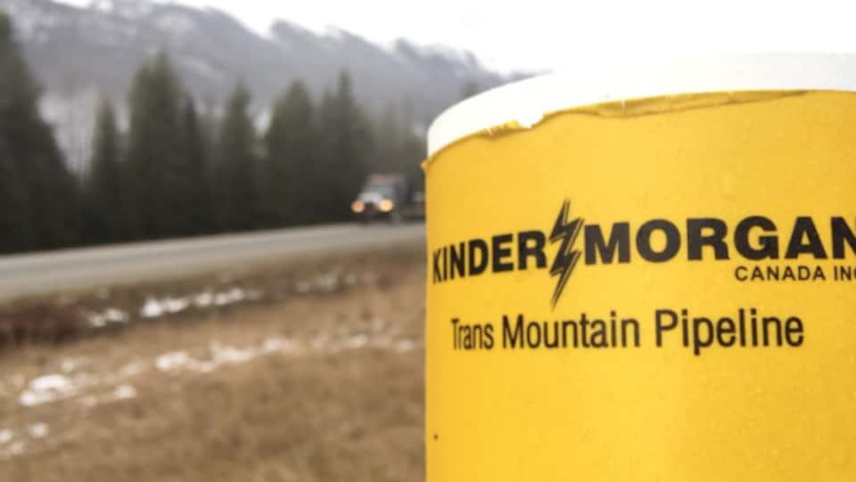 Logo de l'entreprise Kinder Morgan en premier plan, en bordure d'une route. L'entreprise Kinder Morgan affirme que l'attente des permis d'expansion du pipeline TransMountain, en Colombie-Britannique, a des répercussions coûteuses pour le projet.