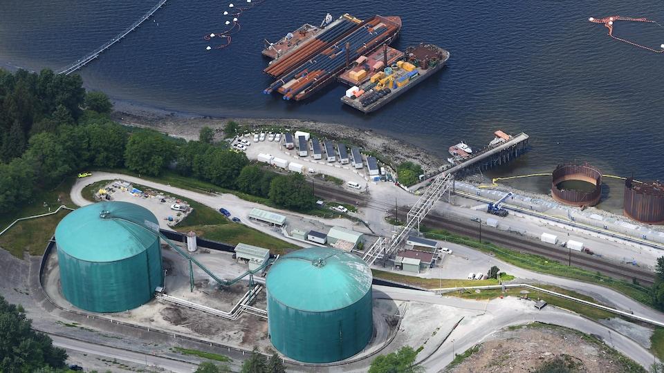 Vue aérienne du terminal, avec deux réservoirs de pétrole et des barges sur lesquelles se trouvent des tuyaux d'acier.