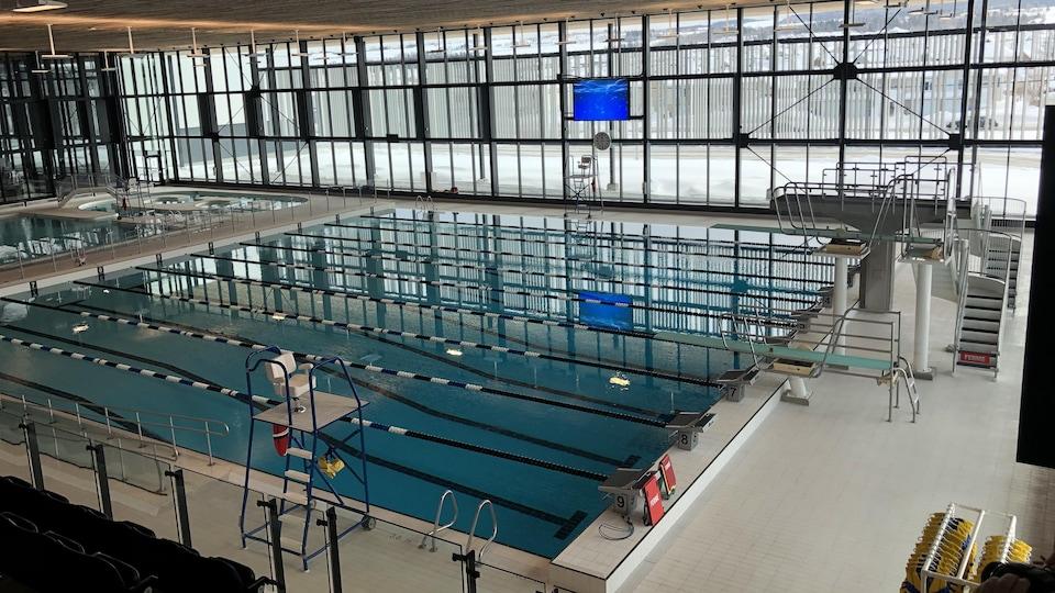 On voit une grande piscine intérieure qui reprend les balises de la piscine olympique avec des tremplins et des corridors en longueur. Derrière elle se trouve une autre zone piscines avec des bassins à remous.