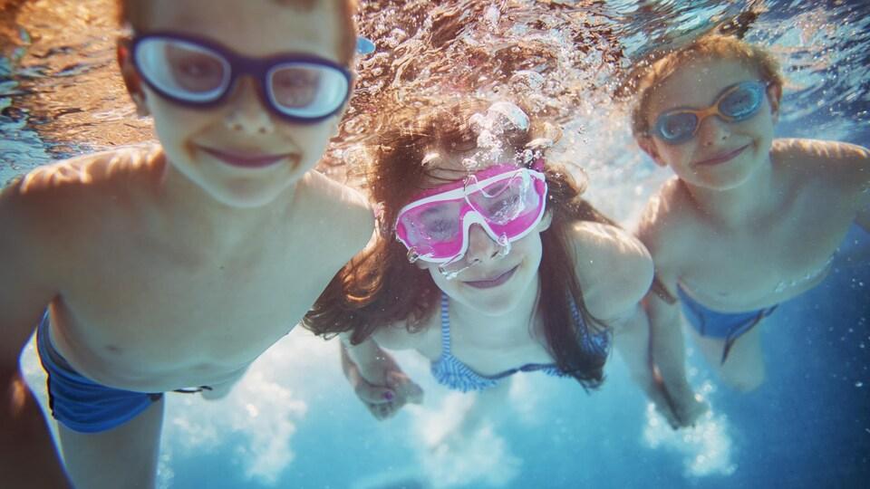 Deux garçons et une fille nagent dans une piscine.
