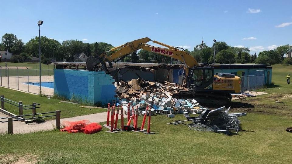 Un excavateur démolit un petit bâtiment bleu.