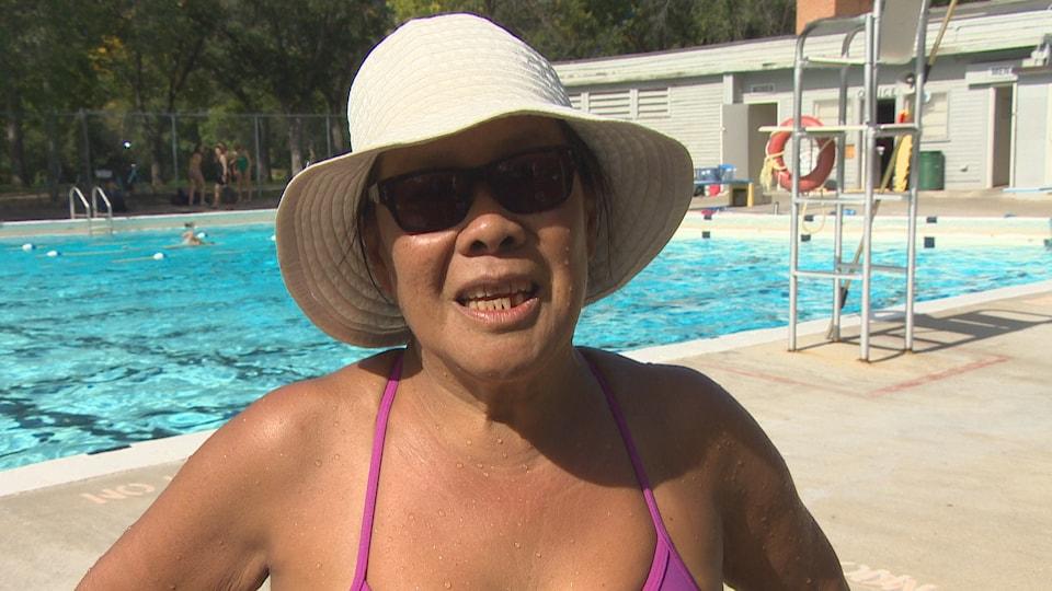 Une femme avec un chapeau en entrevue sur le bord de la piscine.