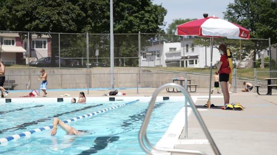 Une sauveteuse supervise la baignade d'enfants dans une piscine.