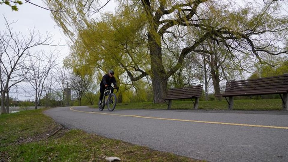 Un homme fait du vélo sur une piste cyclable en bordure d'un cours d'eau.