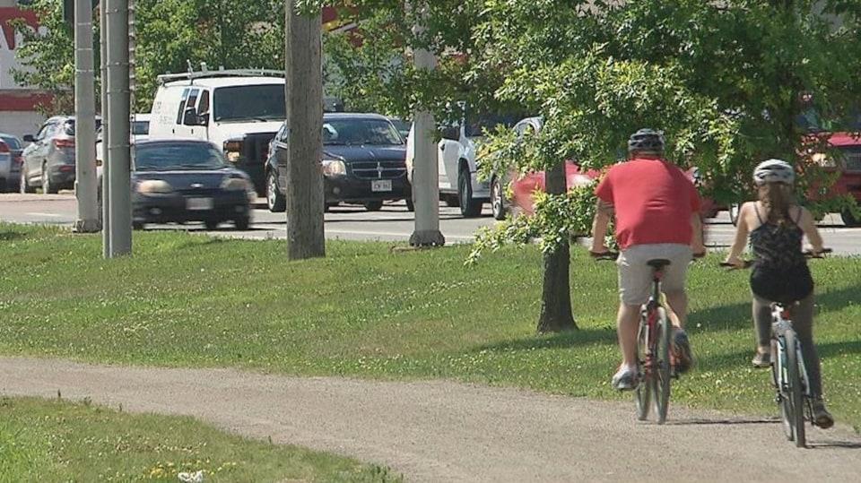 Une piste cyclable avec deux personnes à vélo.