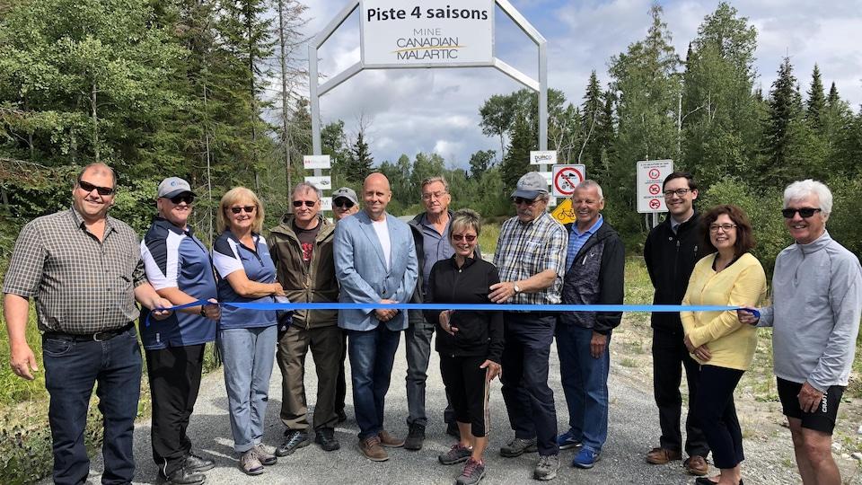 Une dizaine de personnes posent pour la coupe de ruban officielle de la Piste 4 Saisons Mine Canadian Malartic.