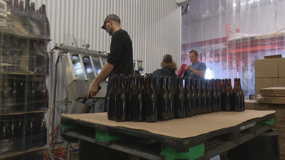 Trois employés nettoient des bouteilles.