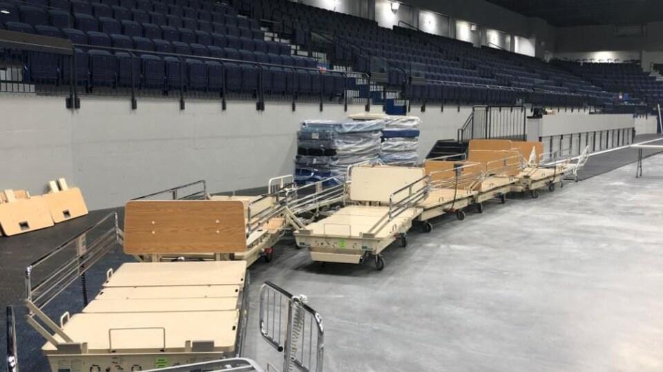 Des lits et de l'équipement sont disposés devant les estrades d'un aréna.