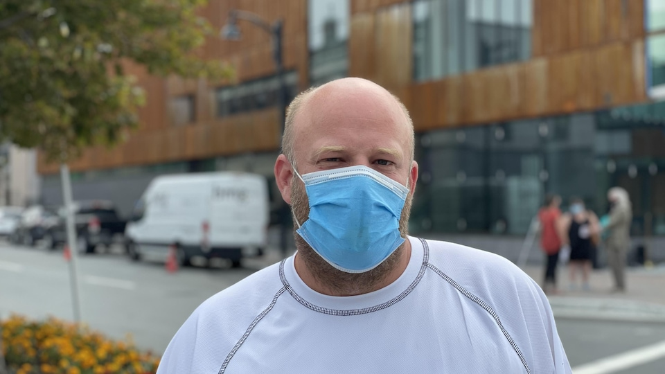Marco Séguin porte un masque et se tient devant un objectif à l'extérieur.