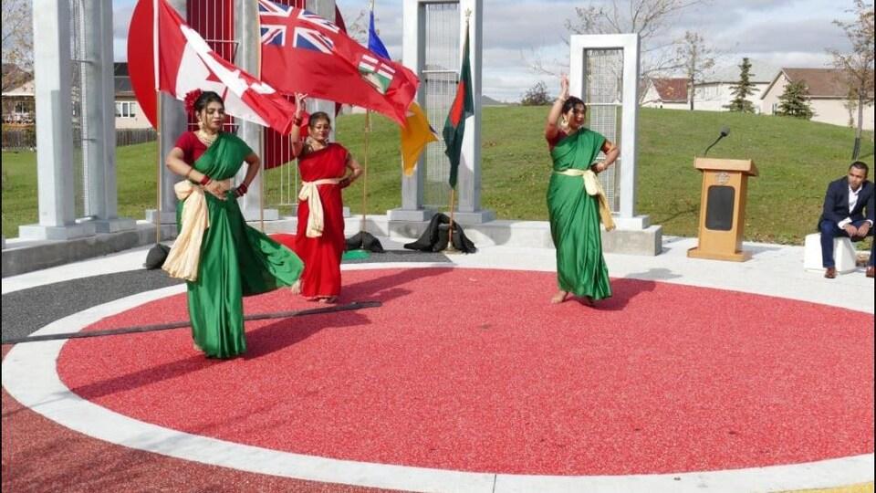Trois danseuses vêtues de robes rouges et vertes dansent.
