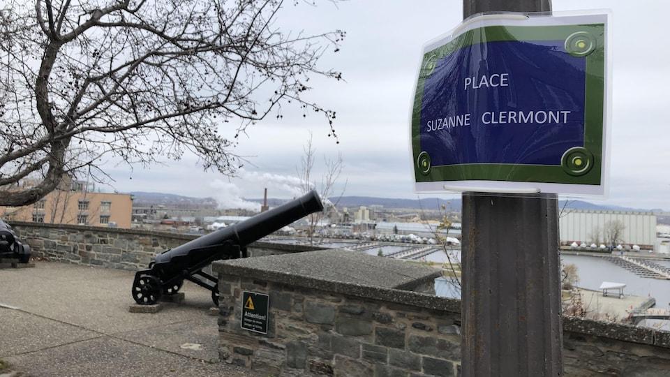 On voit une affiche écrit « Place Suzanne Clermont ».