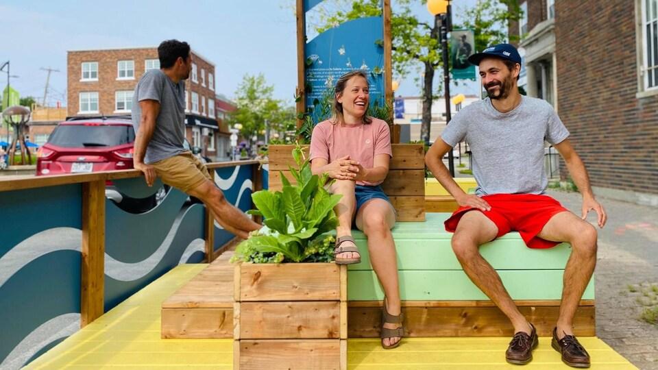 Trois personnes assises sur des bancs sur une terrasse colorée.