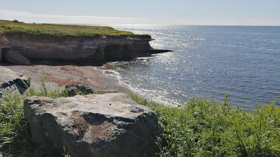 Une petite plage est encastrée entre deux escarpements, et s'ouvre sur le fleuve.