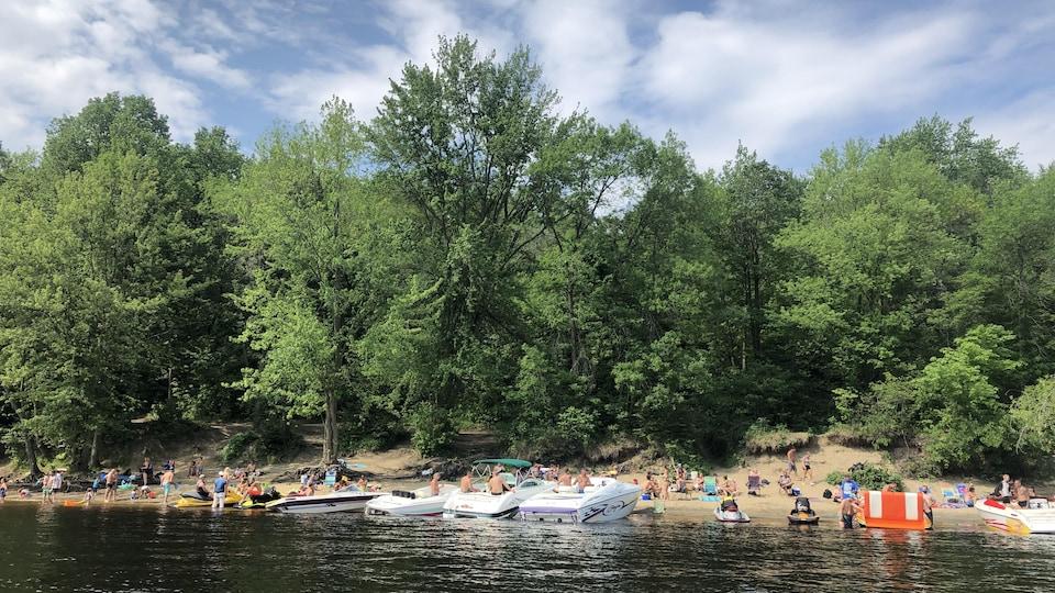 Trois embarcations sont accostées sur une petite plage où plusieurs personnes se baignent.