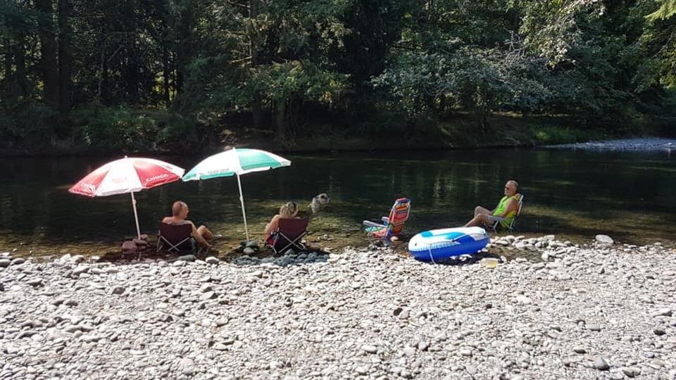 Des touristes sont assis sur des chaises pliantes sur une plage de galets, les pieds dans l'eau.