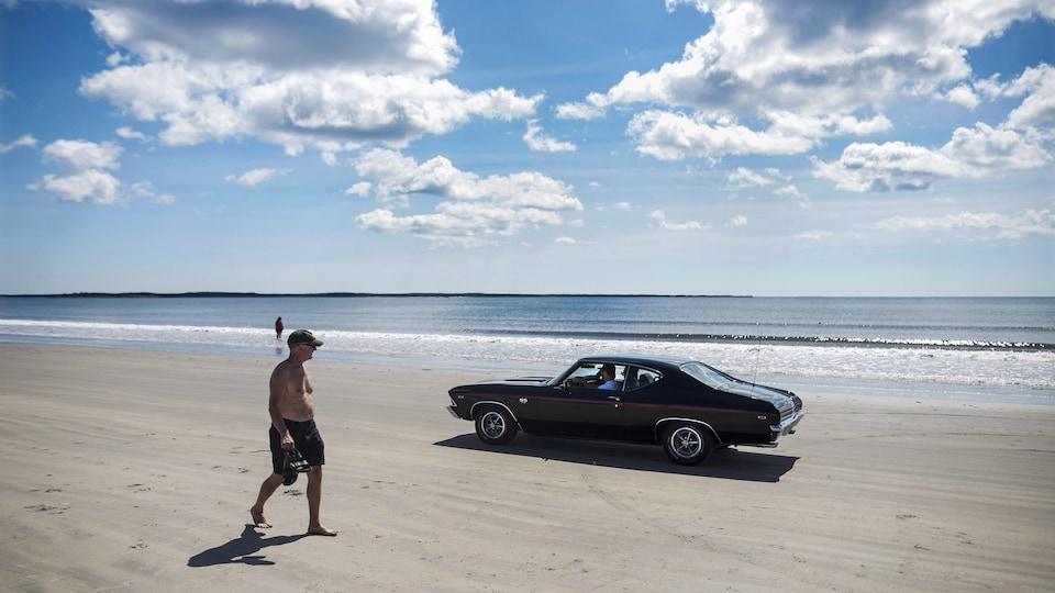 Une voiture rétro passe près d'un homme sur la plage de Crescent Beach, en août 2016.