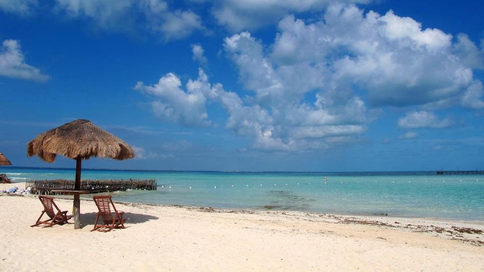 Photo de deux chaises et d'un parasol sur une plage du Mexique sous le ciel bleu