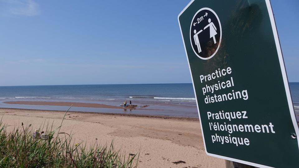 Un panneau avec l'inscription « Pratiquez l'éloignement physique » est placé devant une plage de North Rustico, à l'Île-du-Prince-Édouard.