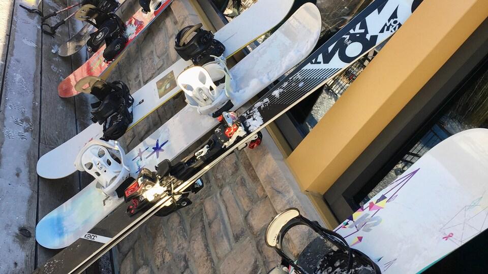 Des planches à neige et des skis sont adossés contre le mur d'un chalet de station de ski.