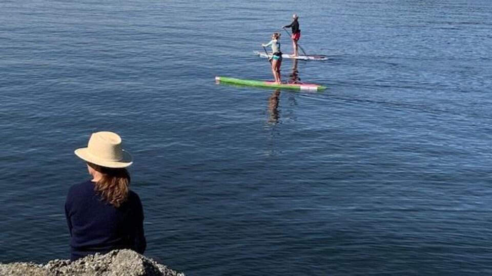 Une dame portant un chapeau est assise sur un rocher pendant que deux autres dames se promènent en planche à pagaie sur un plan d'eau.