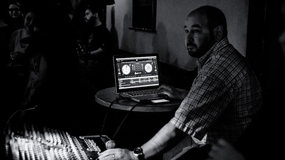 Photo en noir en blanc d'Yves Dumulon assis devant un ordinateur et un panneau de son en train de mixer de la musique.
