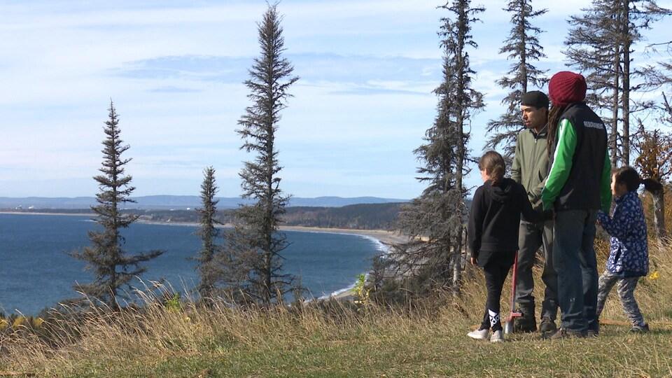 Deux hommes regardent un paysage, en tenant la main de deux fillettes.