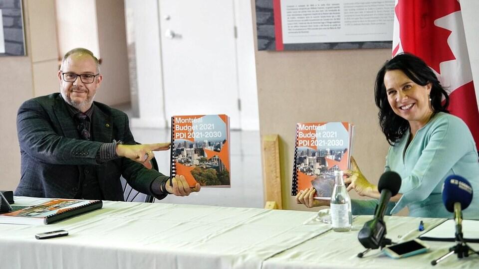 Valérie Plante et Benoît Dorais tiennent chacun un exemplaire du budget 2021 de la Ville de Montréal.