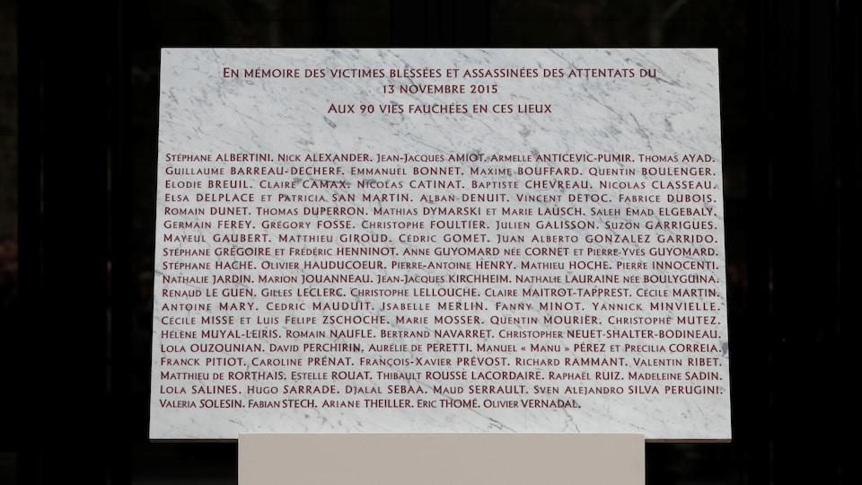 Gros plan de la plaque commémorative, sur laquelle 90 noms sont inscrits.