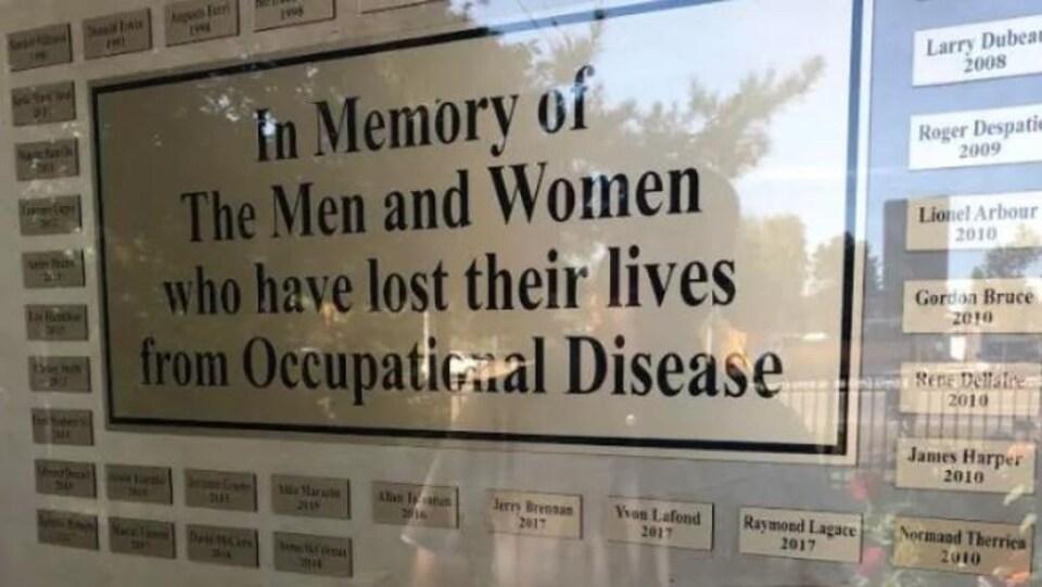 Une plaque sur laquelle sont écrits des noms de personnes décédées