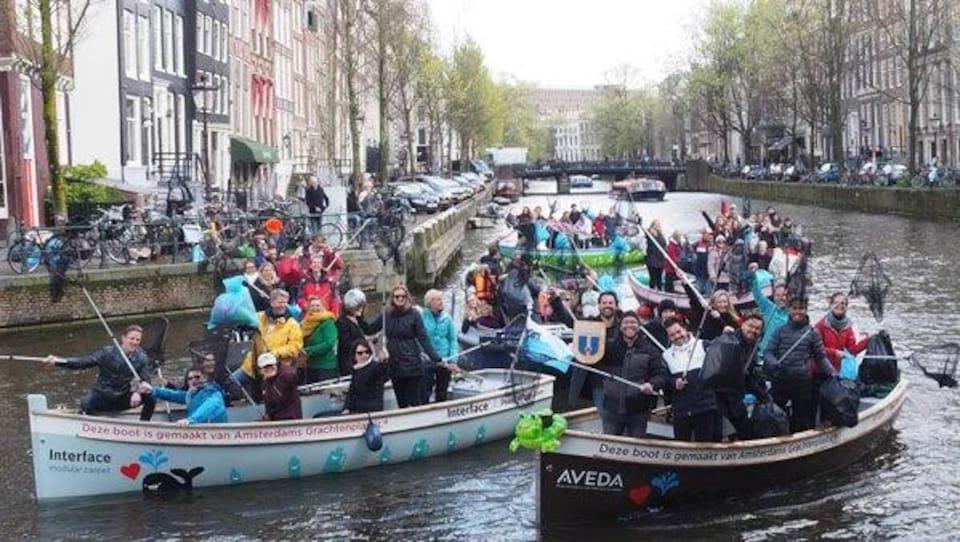 Des touristes sont dans des embarcations pour repêcher les déchets en plastique qui flottent sur les canaux d'Amsterdam.